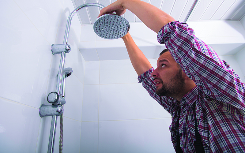 saab plumbing and heating - man fixing bathroom shower head